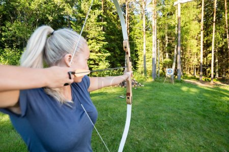 Female Athlete Aiming Arrow At Target Board In Forest