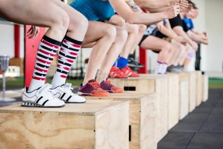 Low Section Of Women Performing Box Jumps With Friends