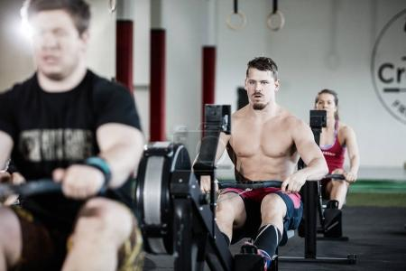 Muscular Man Exercising On Rowing Machine In Gym