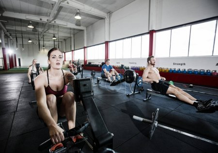 Athlete Using Rowing Machine With Friends In Fitness Center
