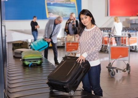 Femme collecte des bagages au tapis roulant à l'aéroport