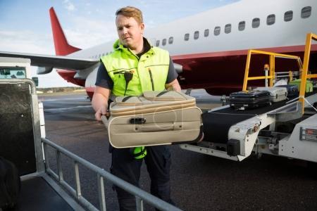 Photo pour Milieu travailleur mâle adulte placer les bagages dans la remorque contre l'avion sur la piste - image libre de droit