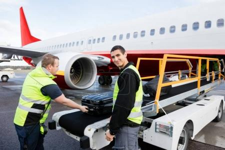 Worker Smiling While Colleague Unloading Luggage On Runway