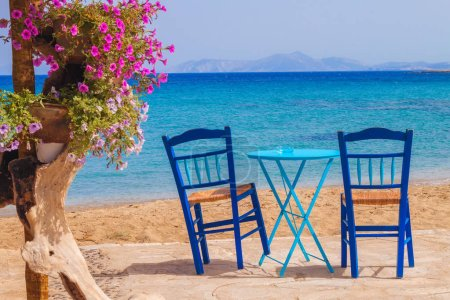 Restaurant table and chairs with a relaxing view of Moutsouna beach, Naxos island, Greece