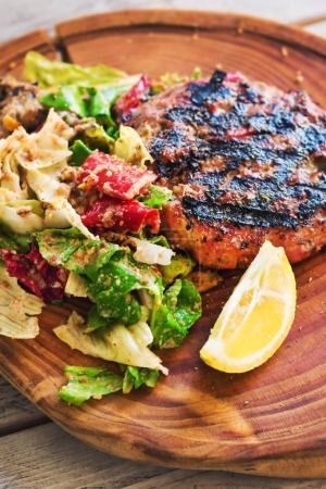 Photo pour Burger à faible teneur en glucides (sans coussin) servi sur une planche en bois rustique avec salade, mise au point sélective - image libre de droit