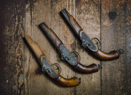 Two vintage pistols on wooden background...