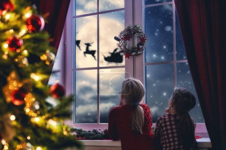 girls sitting by window and looking at Santa