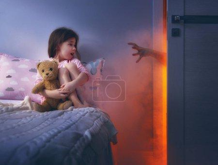 Photo pour Cauchemar pour les enfants. Petite fille enfant a peur des monstres dans l'obscurité de la nuit. - image libre de droit