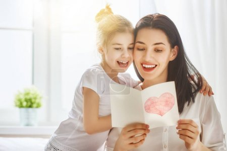 Photo for Happy mother's day! Child daughter congratulates mom and gives her postcard. Mum and girl smiling and hugging. Family holiday and togetherness. - Royalty Free Image