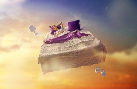 Photo pour Les rêves de femme. Jolie fille vole dans son lit creux ciel étoilé . - image libre de droit