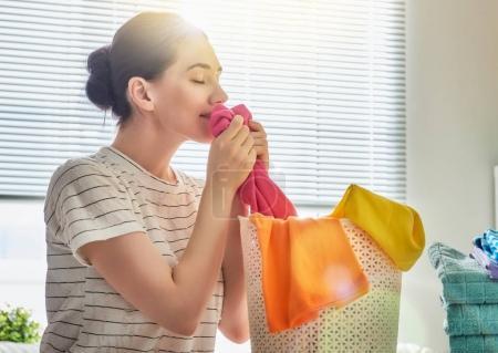 Photo pour Belle jeune femme sent les vêtements propres et souriant tout en faisant la lessive à la maison . - image libre de droit