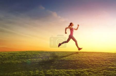 Photo for Healthy lifestyle and sport concepts. Woman in fashionable sportswear is doing exercise on nature. Girl is jogging on sunset background. - Royalty Free Image