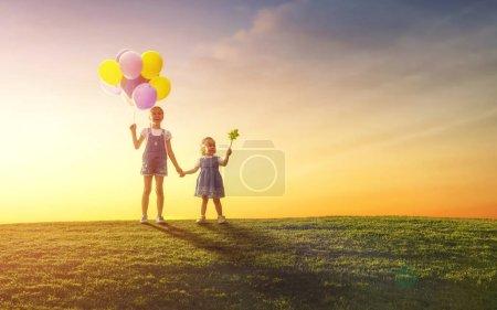 Photo pour Deux heureux petits enfants jouent avec des ballons sur prairie au coucher du soleil. Les sœurs s'amusent et rient de la nature en été . - image libre de droit