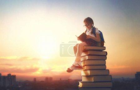 Photo pour Retourne à l'école ! Joyeux enfant industrieux mignon debout sur des livres sur fond de paysage urbain coucher de soleil. Concept d'éducation et de lecture. Le développement de l'imagination . - image libre de droit