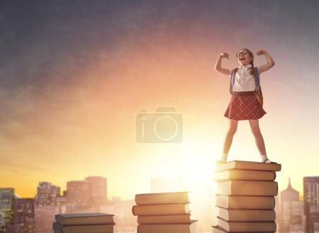 Photo for Back to school! Happy cute industrious child standing on books on background of sunset urban landscape. Concept of education and reading. The development of the imagination. - Royalty Free Image