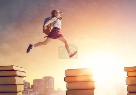 Photo pour Retourne à l'école ! Joyeux enfant industrieux mignon courir et sauter sur des livres sur fond de paysage urbain coucher de soleil. Concept d'éducation et de lecture. Le développement de l'imagination . - image libre de droit