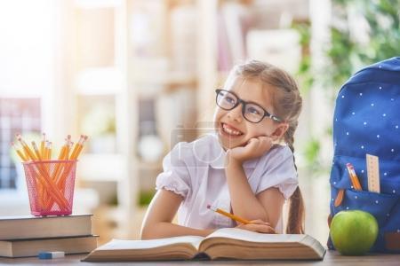 Photo pour Retourne à l'école ! Joyeux enfant industrieux mignon est assis à un bureau à l'intérieur. Le gamin apprend en classe . - image libre de droit