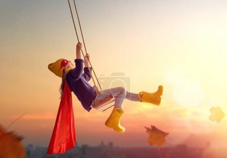 Photo pour Enfant heureux avec balançoire en automne coucher de soleil. Petit enfant qui joue à l'automne sur la promenade dans la nature. Jeune fille en costume de super héros. - image libre de droit