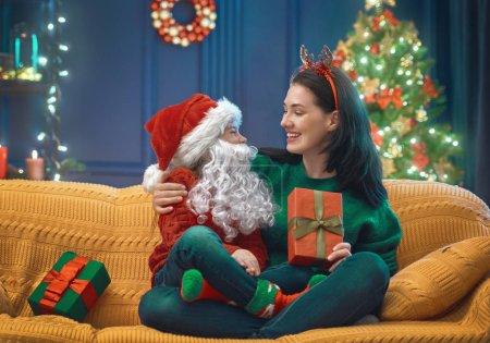 Photo pour Joyeux Noël et Joyeuses Fêtes ! Joyeux maman et sa fille mignonne fille échanger des cadeaux. Parent et petit enfant s'amusent près de l'arbre à l'intérieur. Famille aimante avec des cadeaux dans la chambre . - image libre de droit
