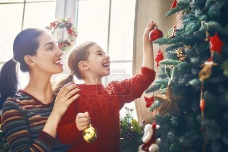 Photo pour Joyeux Noël et Joyeuses Fêtes ! Maman et fille décorent l'arbre à l'intérieur. Le matin avant Noël. Portrait famille aimante gros plan . - image libre de droit