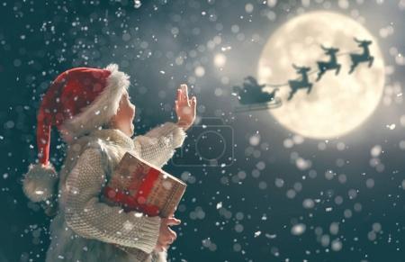 Photo pour Joyeux Noël ! Petit enfant mignon avec cadeau de Noël. Le Père Noël volant dans son traîneau contre le ciel lunaire. Heureux gamin profiter des vacances. Portrait de fille avec des cadeaux sur fond sombre . - image libre de droit