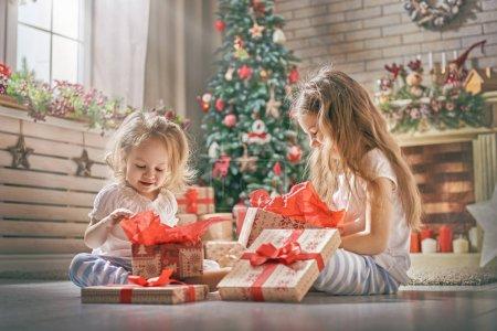 Photo pour Joyeux Noël et Joyeuses Fêtes ! joyeux mignon enfants filles ouverture cadeaux. Les enfants en pyjama s'amusent près de l'arbre le matin. Famille aimante avec des cadeaux dans la chambre . - image libre de droit