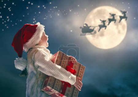 Photo for Merry Christmas! Cute little child with xmas present. Santa Claus flying in his sleigh against moon sky. Happy kid enjoy the holiday. Portrait of girl with gifts on dark background. - Royalty Free Image
