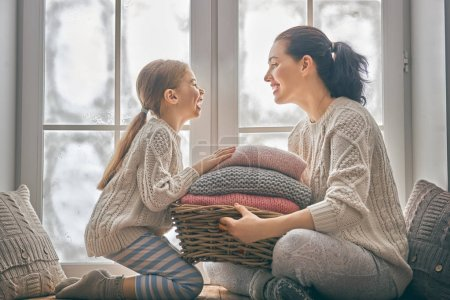 Photo for Winter portrait of happy loving family wearing knitted sweaters. Mother and child girl having fun, playing and laughing at home. Fashion concept. - Royalty Free Image