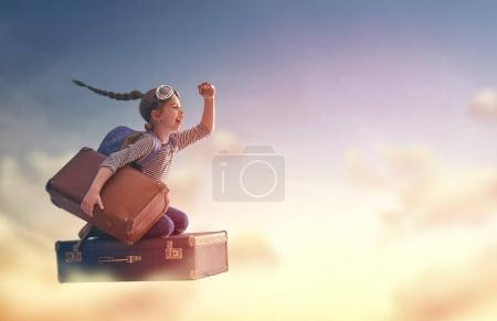 Photo for Dreams of travel! Child flying on a suitcase against the backdrop of sunset - Royalty Free Image