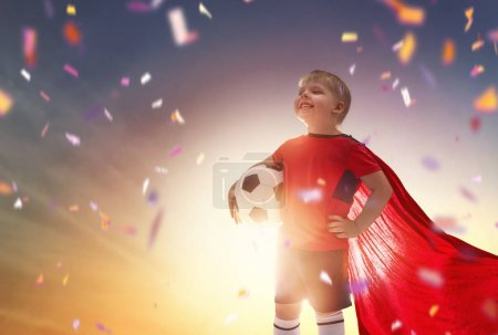 Photo for Cute little child dreaming of becoming a soccer player. Boy playing football on sunset. - Royalty Free Image