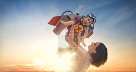 Photo for Mother and her child playing together. Girl in an astronaut costume dreaming of becoming a spaceman. Happy loving family having fun. - Royalty Free Image
