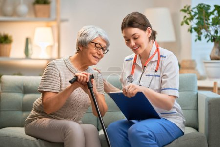Photo for Happy patient and caregiver spending time together. Senior woman holding cane. - Royalty Free Image