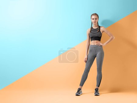 Photo for Healthy lifestyle and sport concepts. Woman in fashionable sportswear is doing exercise. - Royalty Free Image
