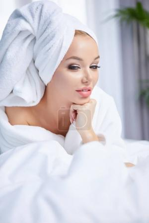 A woman in a bathrobe and a towel on her head