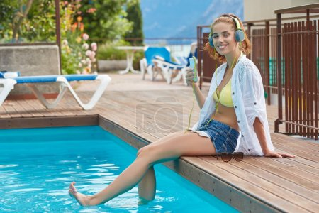 Happy woman relaxing near swimming pool