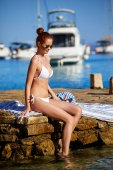 Elegant sexy woman in the white bikini on the sun-tanned slim and shapely body is posing