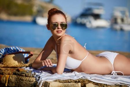 Sexy beautiful woman in white bikini on Mediterranean sea coast