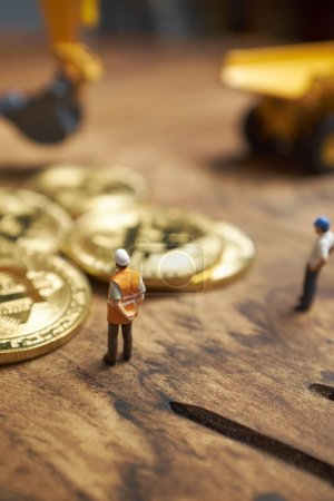 miniature figure people working on Cryptocurrency golden bitcoin