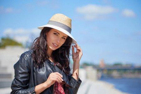 Foto de Retrato de feliz sonriente mujer de pie en la plaza en soleado de verano o primavera, linda mujer sonriente mirando a usted - Imagen libre de derechos