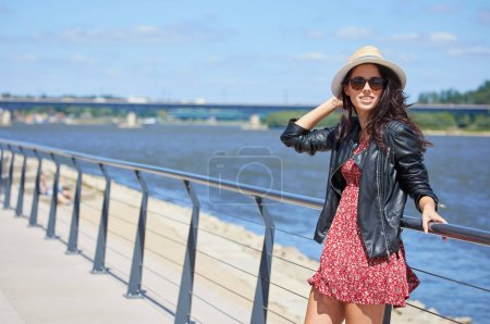 Portrait of happy smiling woman standing on sunny summer day outside, cute smiling woman