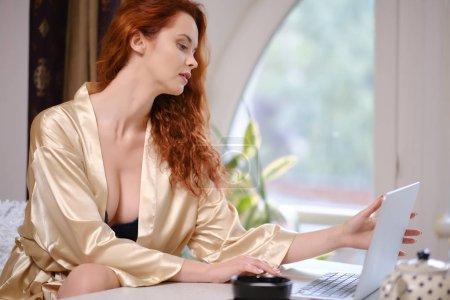 Photo pour Jolie belle femme travaillant sur un ordinateur portable à la fenêtre de la maison - image libre de droit