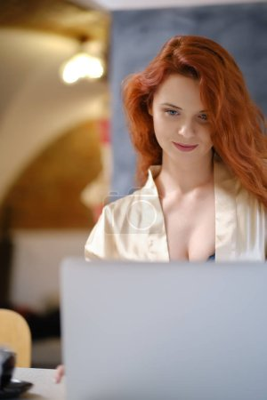 Photo for Young woman wearing a dressing gown sitting comfortably with laptop searching hotel accommodations - Royalty Free Image