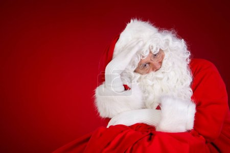 Photo for Santa Claus with huge bag full of christmas presents isolated on red background - Royalty Free Image