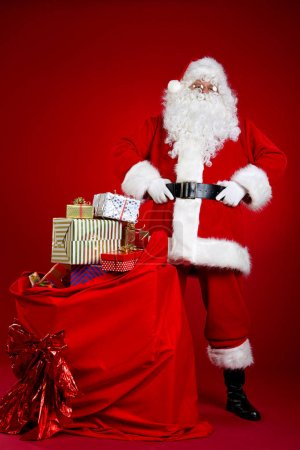 Photo for Santa Claus comes with a big bag of gifts. Full length portrait. - Royalty Free Image