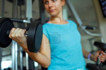Woman with dumbbells in the gym doing sport exercises