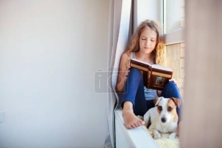 Photo pour Un livre pour enfants à la maison. Fille assise à la fenêtre à lire - image libre de droit