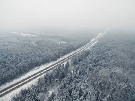 Road in the frozen winter forest with driving cars. Foggy vanishing point perspective. Aerial panoramic view on the north.
