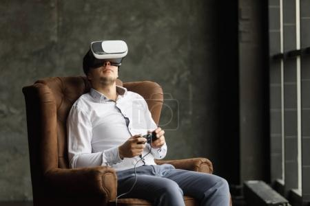 Man wearing virtual reality goggles watching movies or playing video games. The vr headset design is generic and no logos