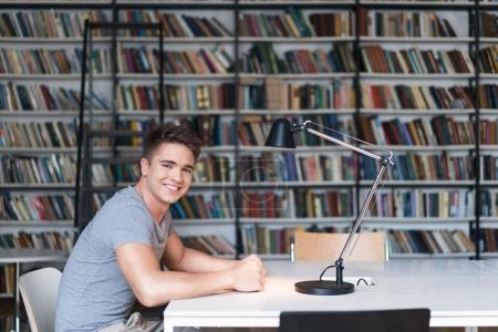 Photo pour Homme souriant avec livre dans la bibliothèque - image libre de droit