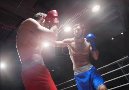 Photo pour Combattre les hommes dans un ring de boxe - image libre de droit